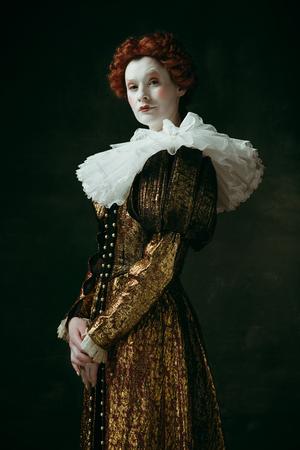 Avere dubbi. Giovane donna rossa medievale in abiti vintage dorati come una duchessa in piedi che incrocia le mani su sfondo verde scuro. Concetto di confronto tra epoche, modernità e rinascimento.
