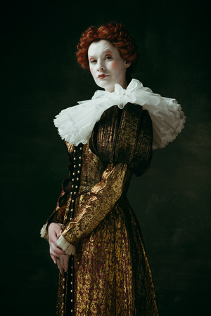 Having doubts. Medieval redhead young woman in golden vintage clothing as a duchess standing crossing hands on dark green background. Concept of comparison of eras, modernity and renaissance.
