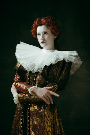 Capricious nature. Medieval redhead young woman in golden vintage clothing as a duchess standing crossing hands on dark green background. Concept of comparison of eras, modernity and renaissance. Stock fotó