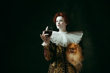 Wishes. Medieval redhead young woman in golden vintage clothing as a duchess holding puppy and glass with red wine on dark green background. Concept of comparison of eras, modernity and renaissance. Stock Photo