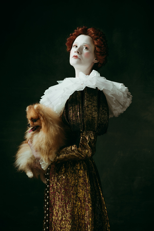 Sign of royalty. Medieval redhead young woman in golden vintage clothing as a duchess holding puppy and standing on dark green background. Concept of comparison of eras, modernity and renaissance. Stock Photo