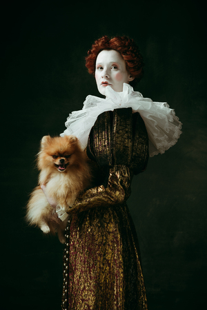Brilliance view. Medieval redhead young woman in golden vintage clothing as a duchess holding puppy and standing on dark green background. Concept of comparison of eras, modernity and renaissance.
