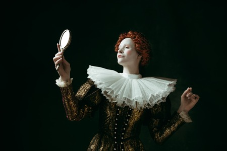 Proud of her self. Medieval redhead young woman in golden vintage clothing as a duchess looking in the mirror on dark green background. Concept of comparison of eras, modernity and renaissance. Archivio Fotografico - 121832577