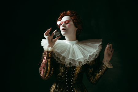 Thin smell. Medieval redhead young woman in golden vintage clothing as a duchess in red sunglasses holding a parfume on dark green background. Concept of comparison of eras, modernity and renaissance. Фото со стока