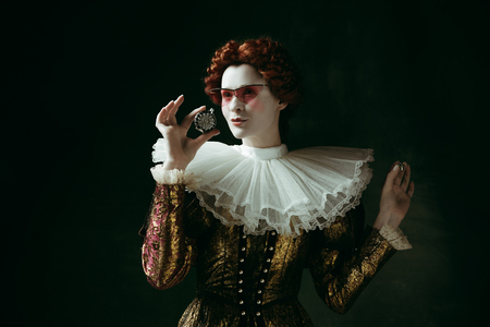 Magic. Medieval redhead young woman in golden vintage clothing as a duchess in red sunglasses holding a parfume on dark green background. Concept of comparison of eras, modernity and renaissance. Stock Photo