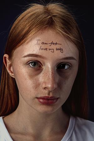 Portret van een jonge vrouw met psychische problemen. Het beeld van een tatoeage op het voorhoofd met de woorden Im fat-love my body. Concept van het verbergen van de ware gevoelens, psychische problemen, behandeling.
