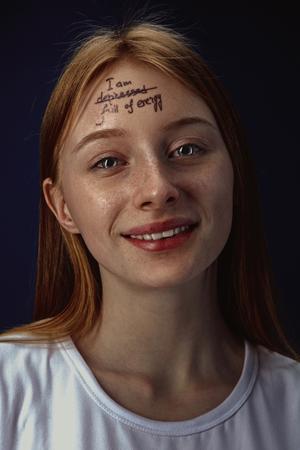 Ritratto di giovane donna che supera i problemi di salute mentale. Tatuaggio sulla fronte con le parole Im depresso-pieno di energia. Concetto di riabilitazione psicologica, ritorno a uno stile di vita sano.