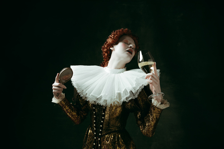 Medieval redhead young woman in golden vintage clothing as a duchess holding a mirror and a glass with white wine on dark green background. Concept of comparison of eras, modernity and renaissance. Archivio Fotografico - 121832601
