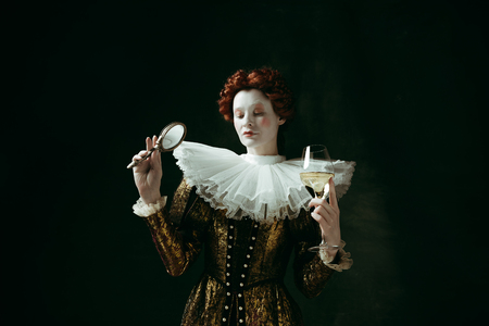 Medieval redhead young woman in golden vintage clothing as a duchess holding a mirror and a glass with white wine on dark green background. Concept of comparison of eras, modernity and renaissance. Archivio Fotografico - 121832602