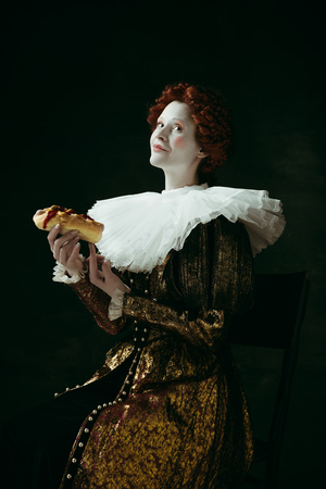 So seductive. Medieval redhead young woman in golden vintage clothing as a duchess eating a hot dog or sandwich on dark green background. Concept of comparison of eras, modernity and renaissance.