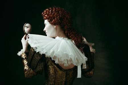Looking for a flaw. Medieval redhead young woman in golden vintage clothing as a duchess looking in the mirror on dark green background. Concept of comparison of eras, modernity and renaissance. Archivio Fotografico - 121832604