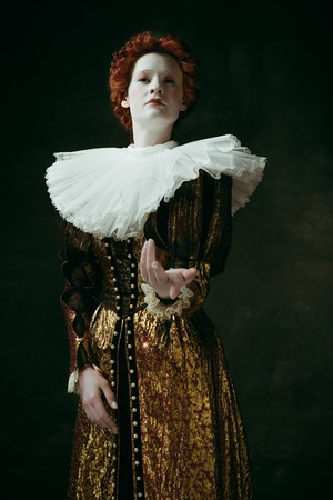 Give it to me. Medieval redhead young woman in golden vintage clothing as a duchess standing pointing up on dark green background. Concept of comparison of eras, modernity and renaissance. Фото со стока
