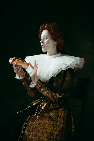 Just a little bit. Medieval redhead young woman in golden vintage clothing as a duchess eating a hot dog or sandwich on dark green background. Concept of comparison of eras, modernity and renaissance. Фото со стока - 121832606