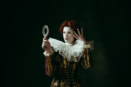 Young and flawless. Medieval redhead young woman in golden vintage clothing as a duchess looking in the mirror on dark green background. Concept of comparison of eras, modernity and renaissance. Archivio Fotografico - 121832607
