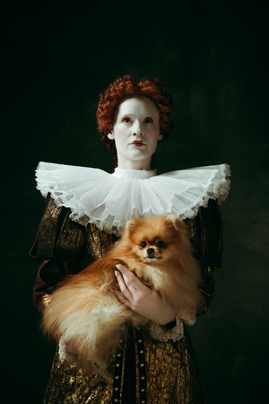 My best friend. Medieval redhead young woman in golden vintage clothing as a duchess holding puppy and standing on dark green background. Concept of comparison of eras, modernity and renaissance. Фото со стока