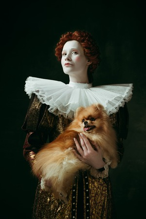 Born to be queen. Medieval redhead young woman in golden vintage clothing as a duchess holding puppy and standing on dark green background. Concept of comparison of eras, modernity and renaissance.