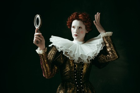 Imagine the crown. Medieval redhead young woman in golden vintage clothing as a duchess looking in the mirror on dark green background. Concept of comparison of eras, modernity and renaissance.