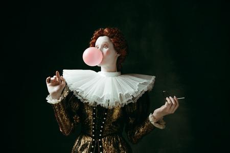Joven pelirroja medieval en ropa vintage dorada como una duquesa con gafas de sol rojas soplando un chicle sobre fondo verde oscuro. Concepto de comparación de épocas, modernidad y renacimiento. Foto de archivo