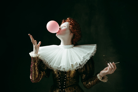 Medieval redhead young woman in golden vintage clothing as a duchess with red sunglasses blowing a bubblegum on dark green background. Concept of comparison of eras, modernity and renaissance. Stock Photo