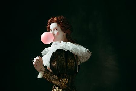 Giovane donna rossa medievale in abiti vintage dorati come duchessa con occhiali da sole rossi che soffia una gomma da masticare su sfondo verde scuro. Concetto di confronto tra epoche, modernità e rinascimento.
