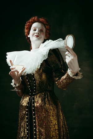 Medieval redhead young woman in golden vintage clothing as a duchess holding a mirror and a glass with white wine on dark green background. Concept of comparison of eras, modernity and renaissance.