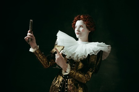 Medieval redhead young woman in golden vintage clothing as a duchess holding a mirror and a glass with white wine on dark green background. Concept of comparison of eras, modernity and renaissance. Archivio Fotografico - 121832707