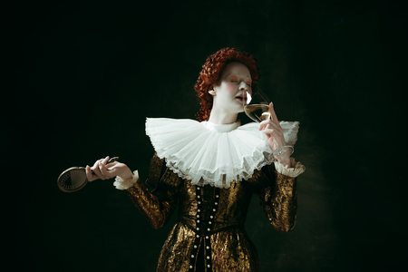 Medieval redhead young woman in golden vintage clothing as a duchess holding a mirror and a glass with white wine on dark green background. Concept of comparison of eras, modernity and renaissance. Archivio Fotografico - 121832709
