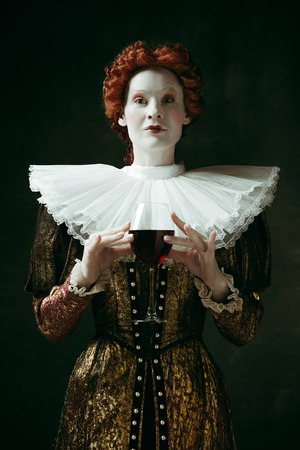 Ideal balance. Medieval redhead young woman in golden vintage clothing as a duchess holding a glass with red wine on dark green background. Concept of comparison of eras, modernity and renaissance.