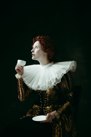 Right choice for a morning. Medieval redhead young woman in golden vintage clothing as a duchess drinking a cup of coffee on dark background. Concept of comparison of eras, modernity and renaissance.