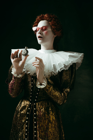 Just a drop. Medieval redhead young woman in golden vintage clothing as a duchess in red sunglasses holding a parfume on dark green background. Concept of comparison of eras, modernity and renaissance.