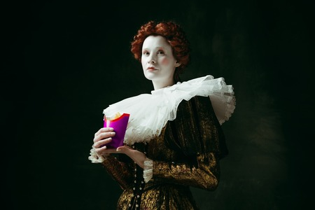 New taste. Medieval redhead young woman in golden vintage clothing as a duchess eating a fried potato on dark green background. Concept of comparison of eras, modernity and renaissance.