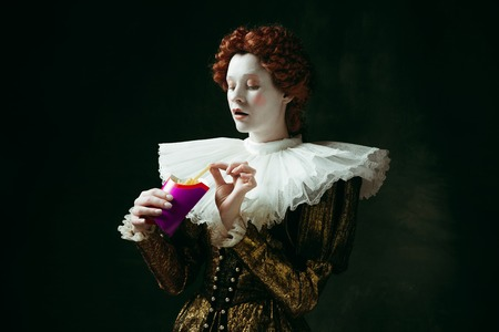 Taste of future. Medieval redhead young woman in golden vintage clothing as a duchess eating a fried potato on dark green background. Concept of comparison of eras, modernity and renaissance.