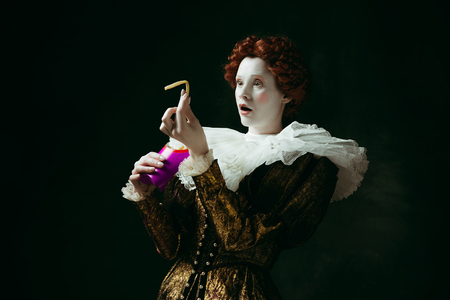 Getting wonder. Medieval redhead young woman in golden vintage clothing as a duchess eating a fried potato on dark green background. Concept of comparison of eras, modernity and renaissance.