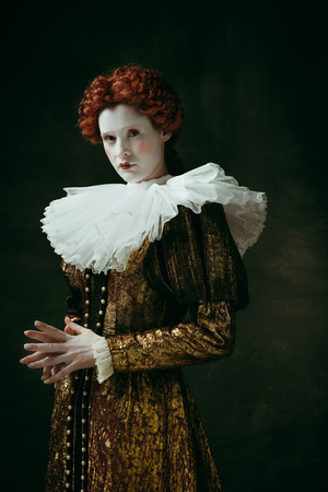 Meditations or thoughts. Medieval redhead young woman in golden vintage clothing as a duchess standing crossing hands on dark green background. Concept of comparison of eras, modernity and renaissance.