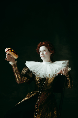 Queens food. Medieval redhead young woman in golden vintage clothing as a duchess eating a hot dog or sandwich on dark green background. Concept of comparison of eras, modernity and renaissance.