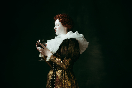 One part of me. Medieval redhead young woman in golden vintage clothing as a duchess holding a glass with red wine on dark green background. Concept of comparison of eras, modernity and renaissance. 写真素材