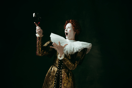 Better than others. Medieval redhead young woman in golden vintage clothing as a duchess holding a glass with red wine on dark green background. Concept of comparison of eras, modernity and renaissance. Stock Photo