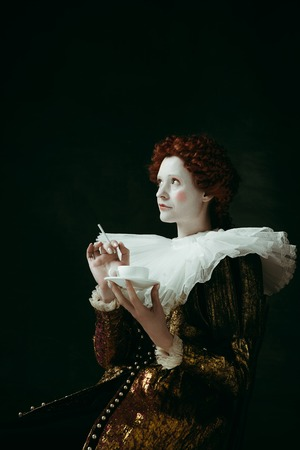 Medieval redhead young woman in golden vintage clothing as a duchess holding a cigarette and a cup of coffee on dark green background. Concept of comparison of eras, modernity and renaissance. Фото со стока