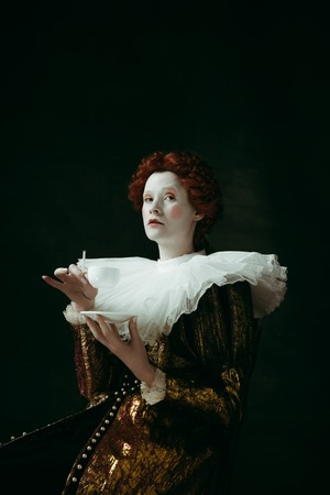 Medieval redhead young woman in golden vintage clothing as a duchess holding a cigarette and a cup of coffee on dark green background. Concept of comparison of eras, modernity and renaissance. 免版税图像
