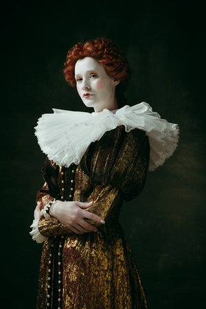 I am the one. Medieval redhead young woman in golden vintage clothing as a duchess standing crossing hands on dark green background. Concept of comparison of eras, modernity and renaissance.