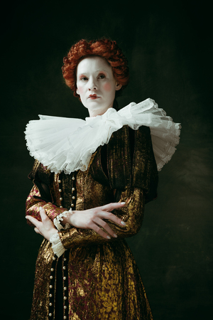 Too serious. Medieval redhead young woman in golden vintage clothing as a duchess standing crossing hands on dark green background. Concept of comparison of eras, modernity and renaissance.