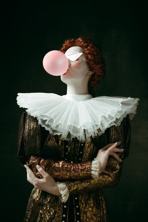 Medieval redhead young woman in golden vintage clothing as a duchess with red sunglasses blowing a bubblegum on dark green background. Concept of comparison of eras, modernity and renaissance. 写真素材