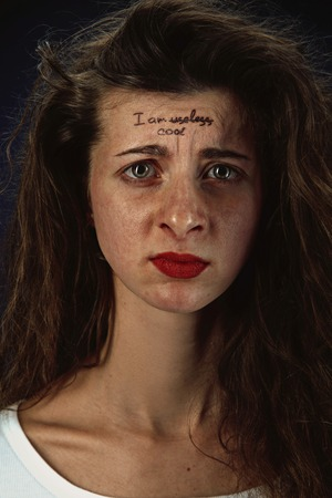 Portrait of young woman with mental health problems. Tattoo on the forehead with the words Im useless-cool. Concept of hidding the true feelings, psycological trouble, treatment.