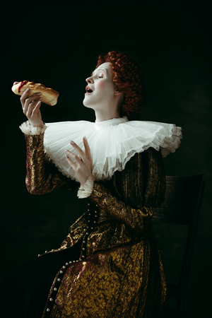 A little trick. Medieval redhead young woman in golden vintage clothing as a duchess eating a hot dog or sandwich on dark green background. Concept of comparison of eras, modernity and renaissance.