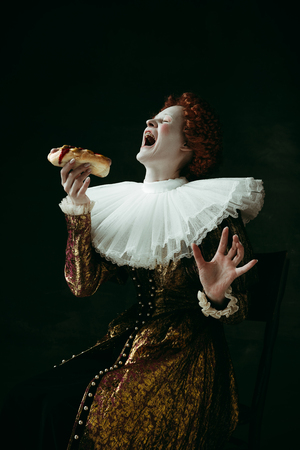 Pure emotions. Medieval redhead young woman in golden vintage clothing as a duchess eating a hot dog or sandwich on dark green background. Concept of comparison of eras, modernity and renaissance. Фото со стока - 121833015
