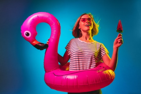 Female half-length portrait on blue neon lights studio background. Woman in red sunglasses and rubber ring as a flamingo with drink and candy. Facial expression, summer, weekend concept. Trendy colors. Фото со стока