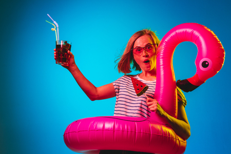 Female half-length portrait on blue neon lights studio background. Woman in red sunglasses and rubber ring as a flamingo with drink and candy. Facial expression, summer, weekend concept. Trendy colors. Stockfoto