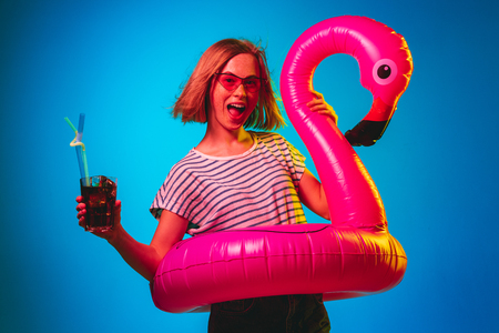 Beautiful female half-length portrait on blue neon lights studio background. Woman in red sunglasses and rubber ring as a flamingo with drink. Facial expression, summer, weekend concept. Trendy colors.