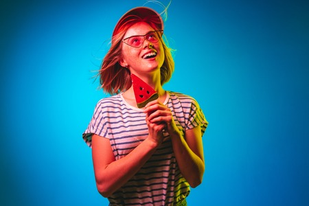 Beautiful female half-length portrait isolated on blue neon lights studio background. Woman in red cap and sunglasses with watermelon candy. Facial expression, summer, weekend concept. Trendy colors.
