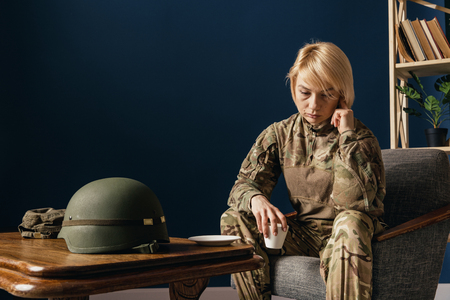 Close up portrait of young female soldier. Woman in military uniform on the war. In doctors consultation, depressed and having problems with mental health and emotions, PTSD, rehabilitation.